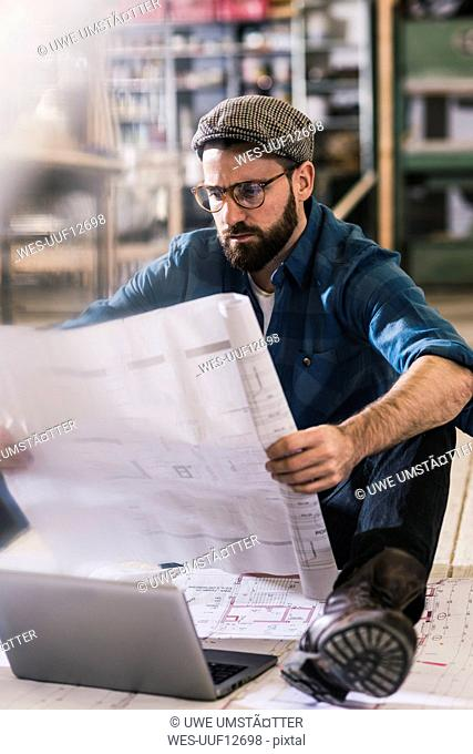 Man sitting on the floor looking at construction plan
