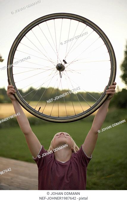 Boy holding bicycle wheel