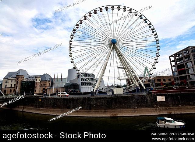 10 June 2020, North Rhine-Westphalia, Cologne: A 55-metre high Ferris wheel of the showman Kipp stands in the Rheinauhafen in Cologne next to the chocolate...