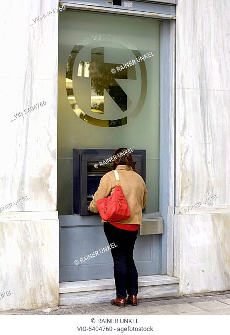 GRC , GREECE : A woman taking money from an ATM cash machine of Alpha Bank in Athens , 08.02.2016 - Athens, Attica, Greece, 08/02/2016