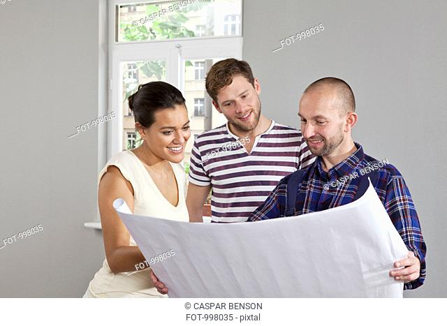 A building contractor showing blueprints to a young couple