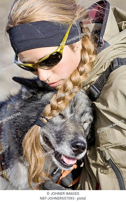 A young woman and a dog on a hiking tour in the mountains, Svalbard, Norway