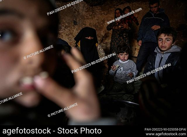 23 February 2020, Syria, Idlib: Syrian children and a woman are pictured inside a cave at Taltouna village. At least eight families live in an ancient deserted...
