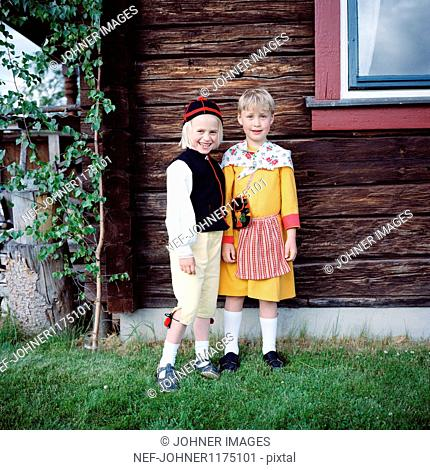 Boy and girl in traditional clothing, smiling, portrait