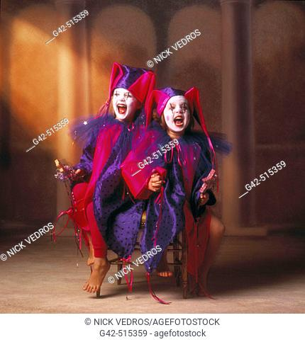 Two young girls wearing jester costumes