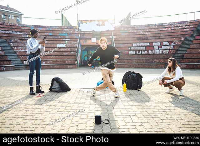 Young dancers rehearsing in a skare park, friends making a video