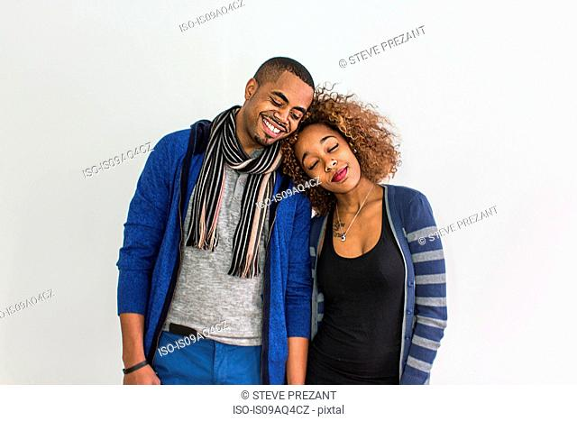 Studio portrait of romantic couple with heads on each others shoulder