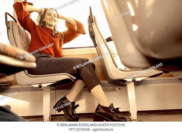 young happy woman sitting in public transport, in city Cottbus, Brandenburg, Germany