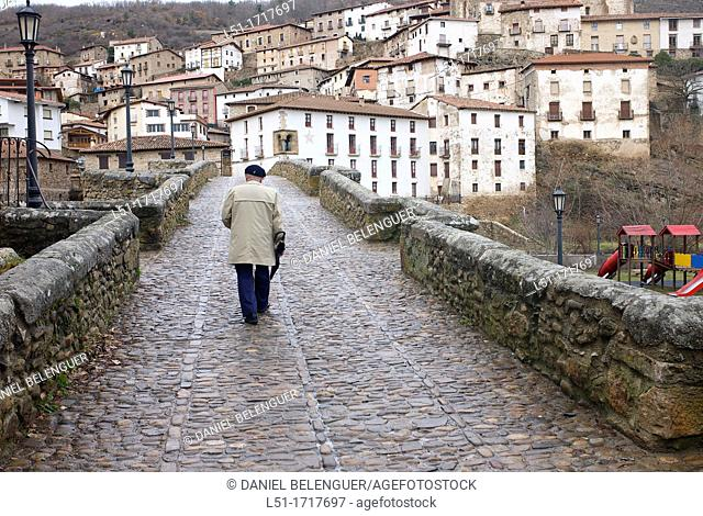 man walking over a bridge in Villoslada de Cameros, Sierra cebollera nature reserve, La Rioja, Spain