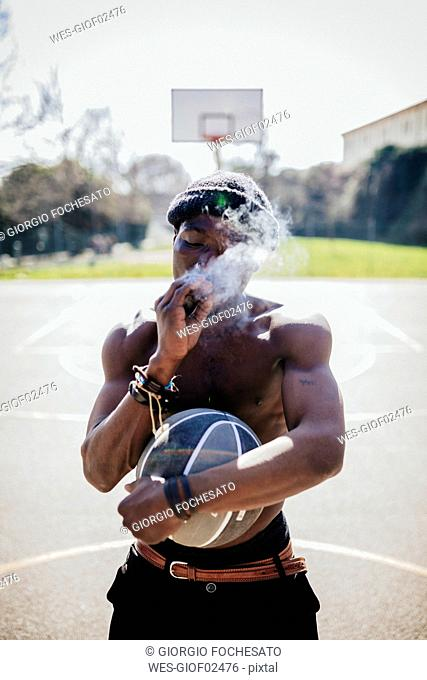 Barechested basketball player on court smoking a joint