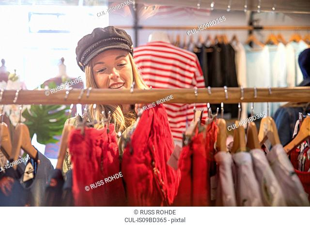 Young woman shopping, looking at clothes on rail in shop