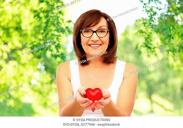 portrait of smiling senior woman holding red heart