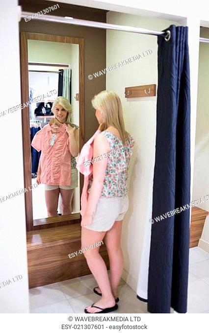 Woman looking in the mirror standing in the changing room
