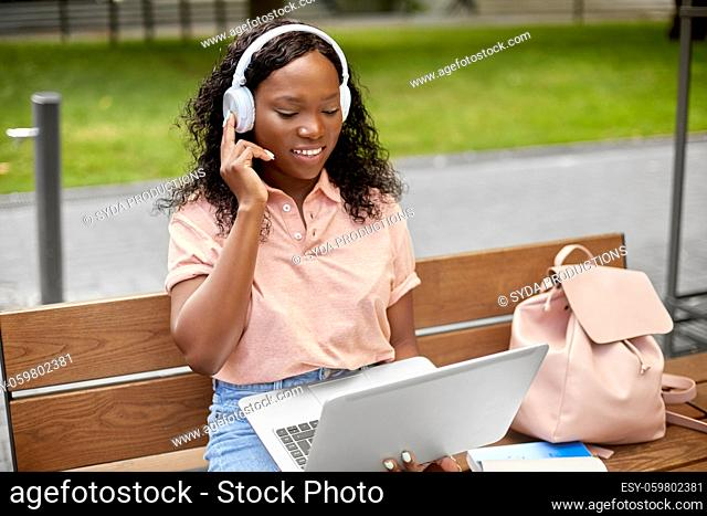 african student girl in headphones with laptop
