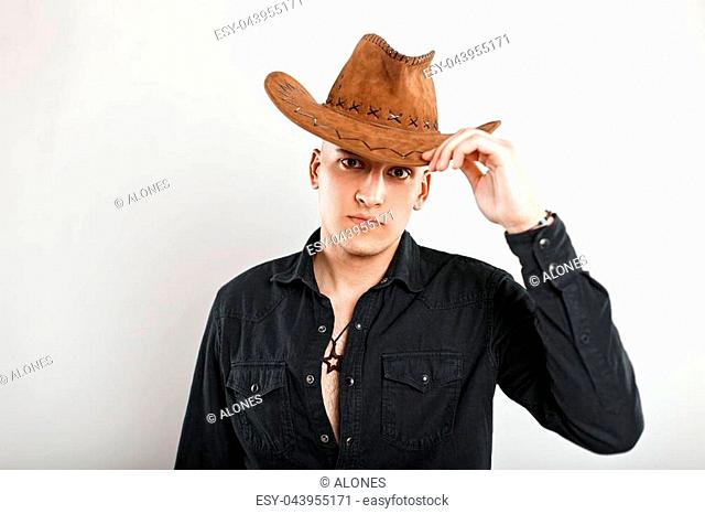 Handsome young man in a black shirt with a cowboy hat on a white background