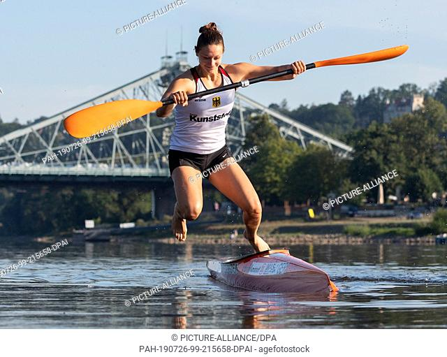 25 July 2019, Saxony, Dresden: Steffi Kriegerstein, Olympic silver medallist in canoeing, jumps into the Elbe after a training session for the World...