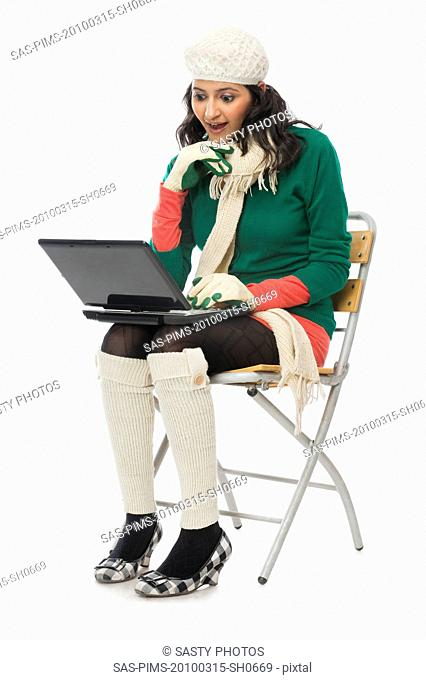 Woman using a laptop and looking surprised