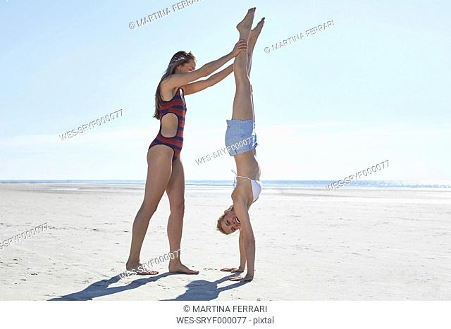 Young woman helping friend doing a handstand on the beach