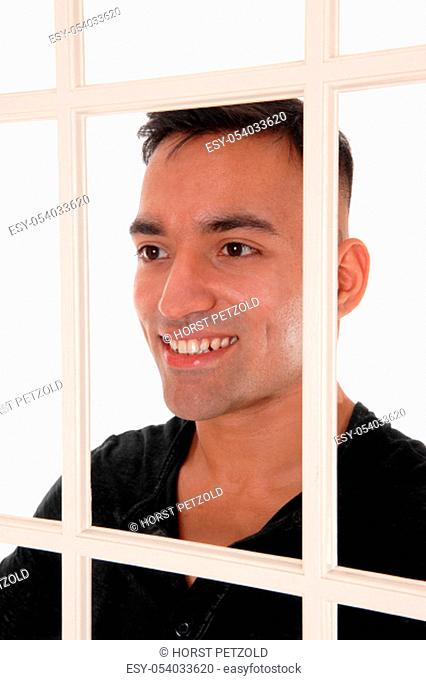 A happy east Indian man standing behind a white window frame in a.black dress shirt with a big smile, isolated for white background