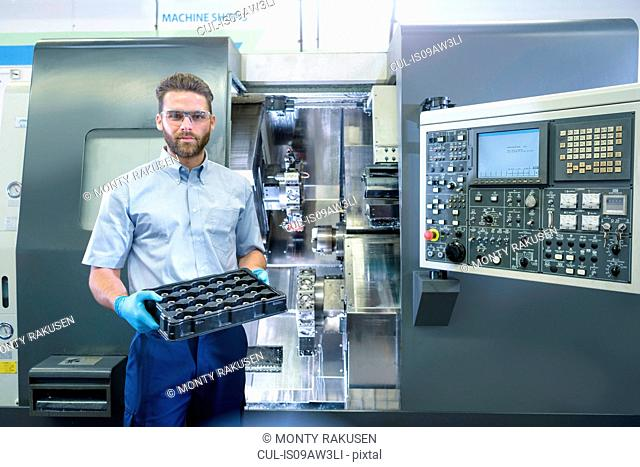 Portrait of engineer with CNC lathe in automotive parts factory