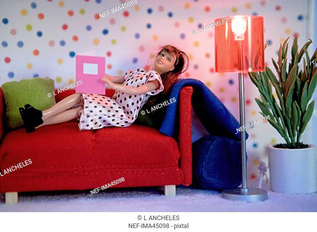 A doll in a sofa in a doll house