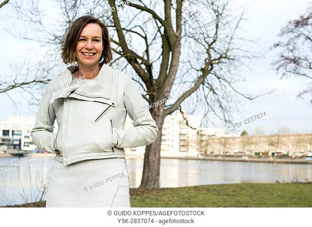 The Hague, Netherlands. Portrait of a caucasian woman standing in a park with hands inside her leather jacket pockets