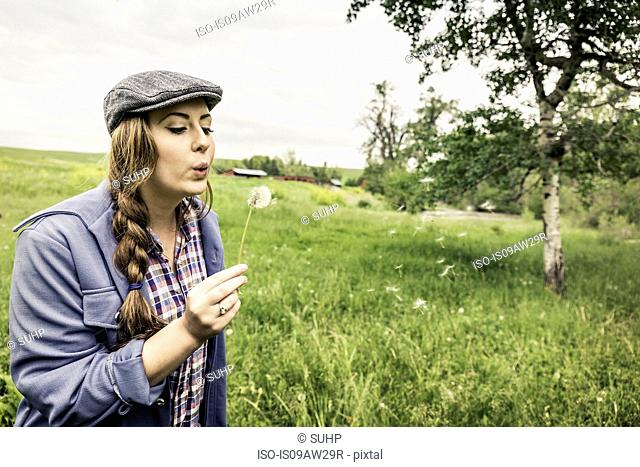 Young woman with plait wearing flat cap in field blowing dandelion seeds