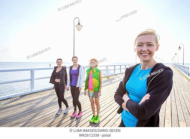 Group of women in sports clothing standing on jetty
