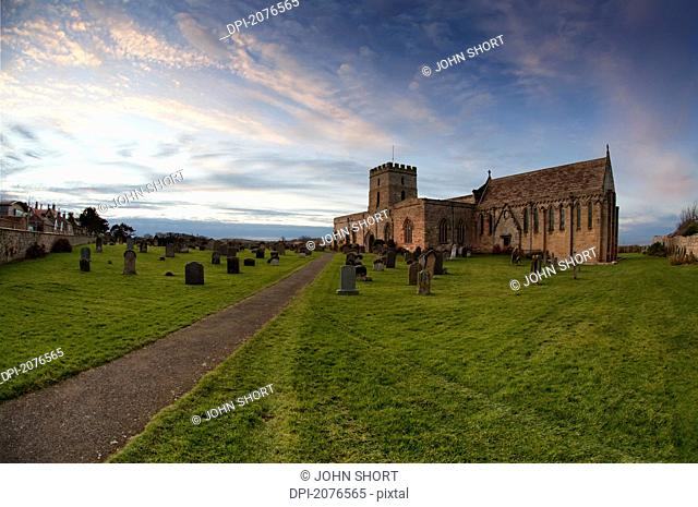 Path leading to a church building and cemetery, bamburgh northumberland england