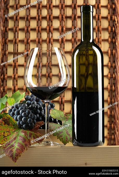 red wine bottle, glass, grapes, wicker background