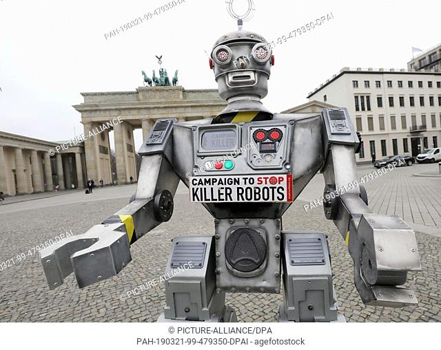 "21 March 2019, Berlin: A robot stands in front of the Brandenburg Gate. The replica is part of an international campaign of the NGO """"Facing Finance"""" to ban..."