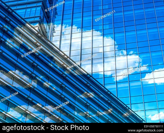 modern glass building with clouds and sky reflections