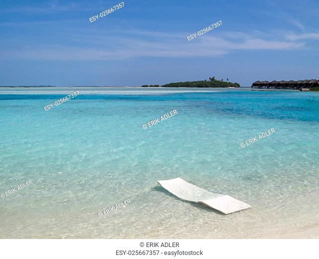overlooking the sea with sun in the water on a beautiful beach in the maldives
