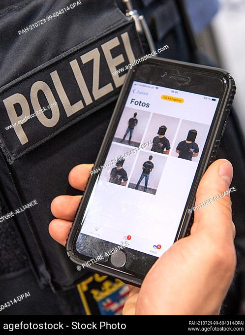 29 July 2021, Hessen, Frankfurt/Main: A police officer shows a special police app with photos of a fictitious suspect on his smartphone for demonstration...