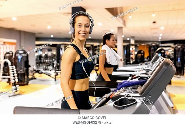 Smiling woman wearing headphones in gym on a treadmil
