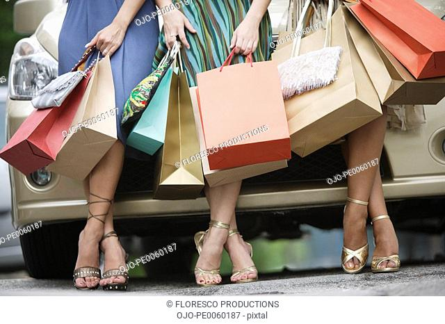 Three women outdoors with shopping bags leaning on car