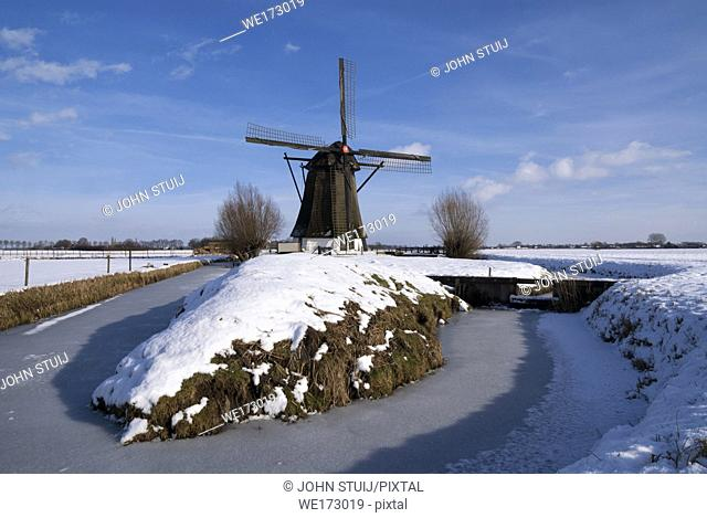 Windmill Oude Doornse Molen in a snow covered landscape near Almkerk in the Dutch province Noord-Brabant