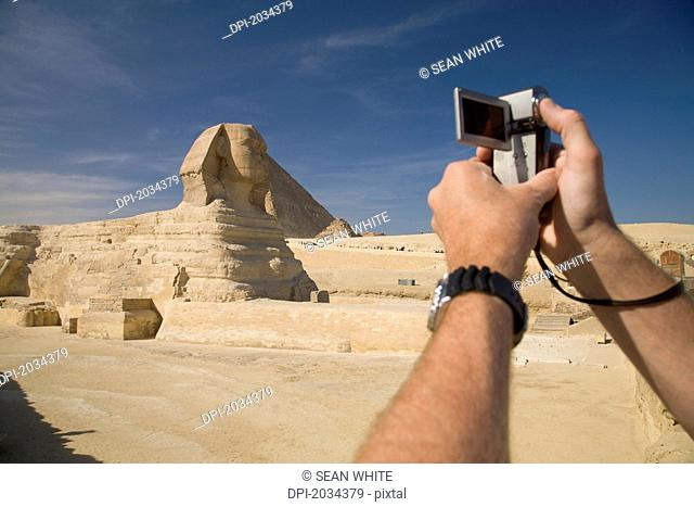 A Man Takes And Photo And Video Footage With A Camera Of The Great Sphinx Of Giza At The Pyramids Of Giza Near Cairo, Giza Egypt