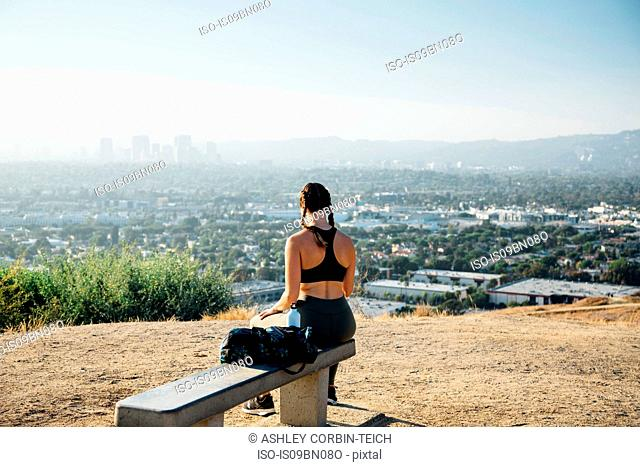 Woman sitting on bench on hilltop, Los Angeles, US