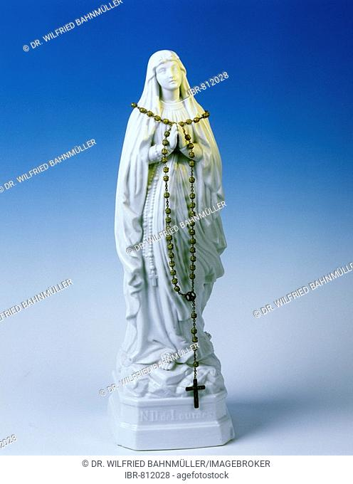 Rosary beads draped over a statue of Our Lady of Lourdes