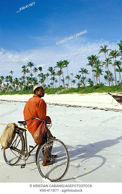 African man leaning on his bicycle at the white sandy beach of the east of Unguja Island, Zanzibar Archipelago, Tanzania, East Africa