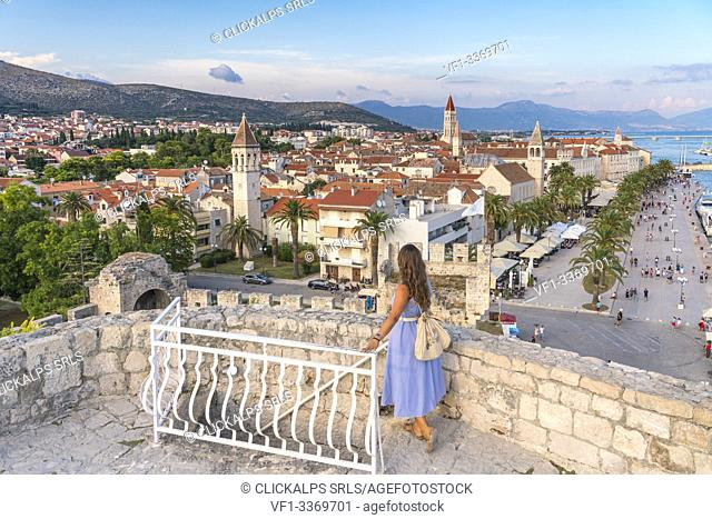 Woman admiring the old town from Karmelengo castle, in summer. Trogir, Split - Dalmatia county, Croatia