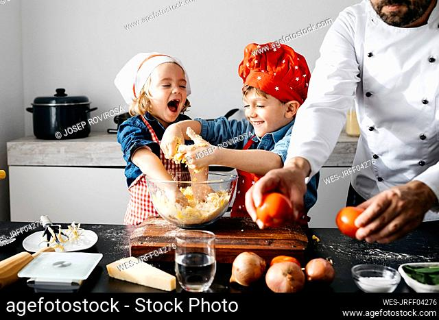 Happy kids preparing dough with father in kitchen at home