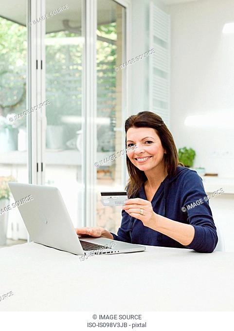Mature woman using laptop with credit card