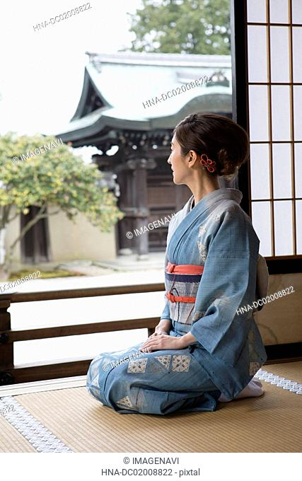 Young Japanese woman in kimono sitting on Tatami