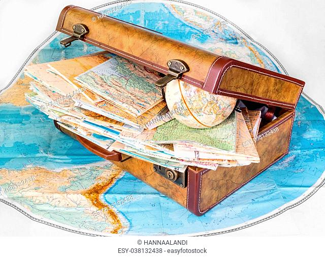 Suitcase and maps of different countries isolated on white background