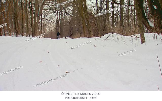 Man walking down snowy path in the woods