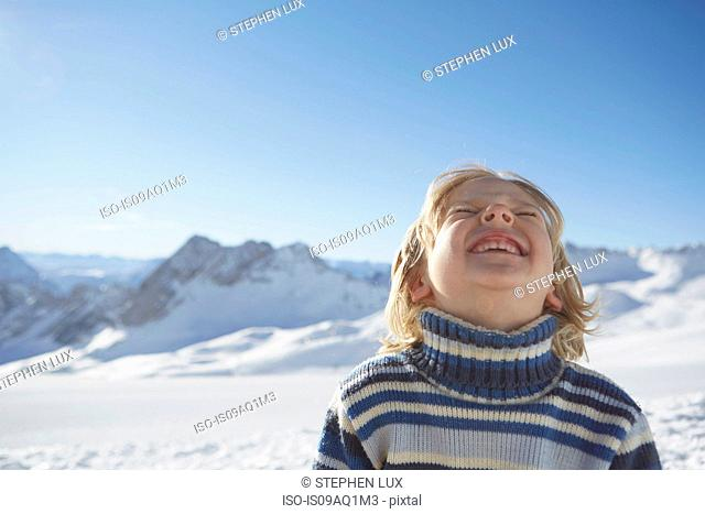 Portrait of young boy in snowy landscape, looking up, smiling