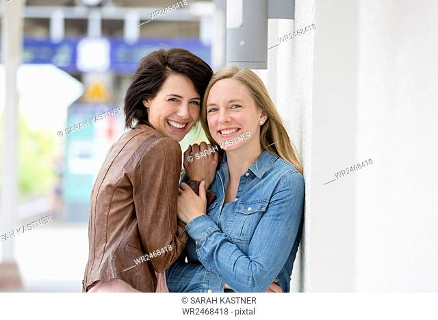 Two girlfriends laugh together and talk