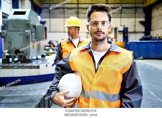 Portrait of serious man wearing protective workwear in factory